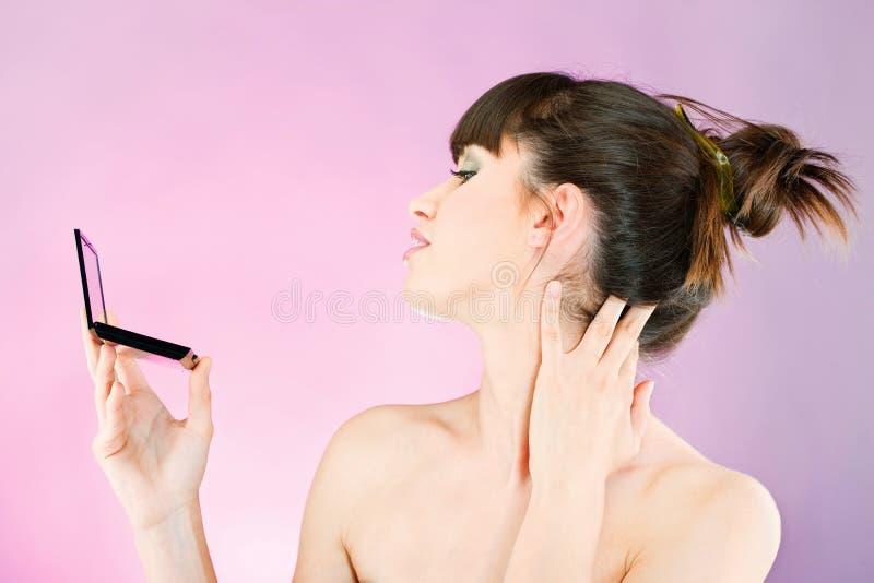Mulher que verifica a pele da face no espelho imagens de stock royalty free