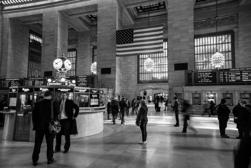 Mulher que verifica a programação dos trens na estação de Grand Central Outros povos que correm ou apenas que falam fotos de stock royalty free