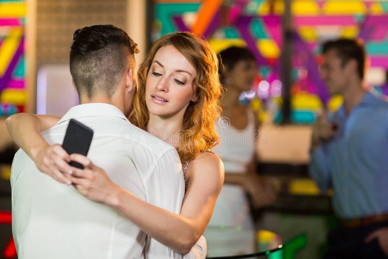 Mulher que verifica seu telefone celular ao abraçar um homem fotografia de stock