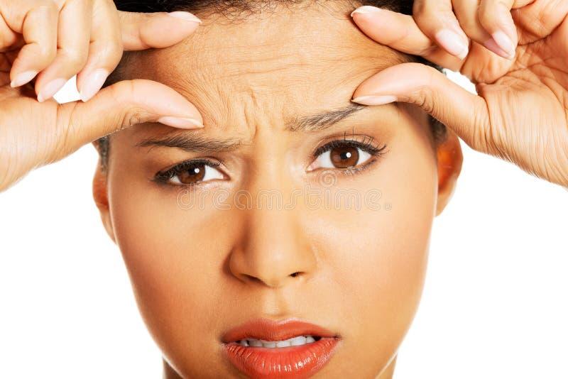 Mulher que verifica seus enrugamentos em sua testa imagens de stock