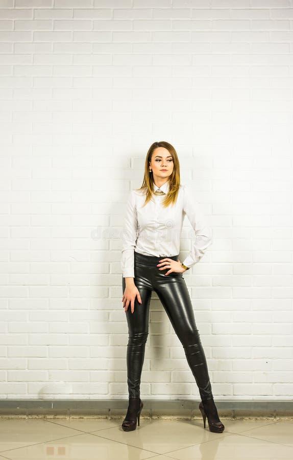 Mulher que veste calças e sapatas de couro pretas do salto alto dentro fotos de stock royalty free