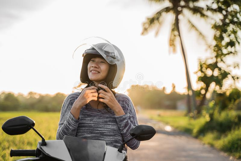 Mulher que veste e para prender seu capacete ao montar fotos de stock