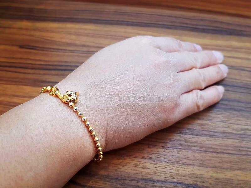 Mulher que veste o bracelete dourado com ornamento da Coração-forma fotografia de stock