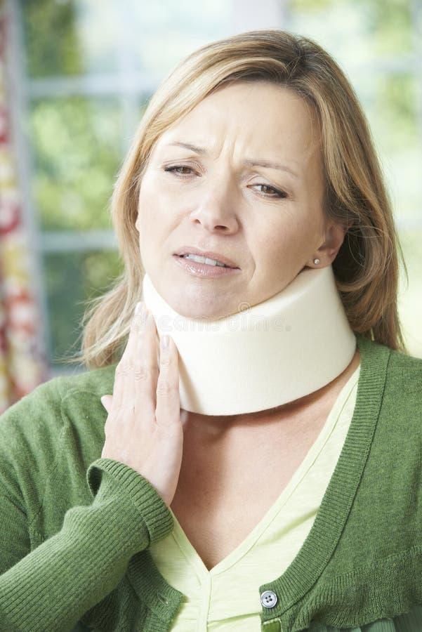 Mulher que veste o colar cirúrgico na dor imagens de stock royalty free
