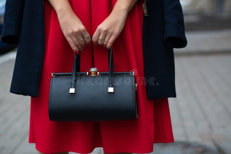Mulher que veste o vestido à moda e o revestimento vermelhos que guardam a bolsa de couro preta Copie o espaço fotos de stock royalty free