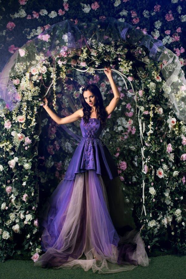 mulher que veste o vestido roxo longo que levanta no jardim florescido fotografia de stock
