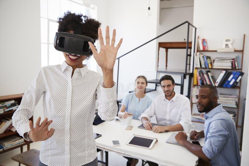 Mulher que veste os óculos de proteção de VR olhados por colegas em um escritório foto de stock
