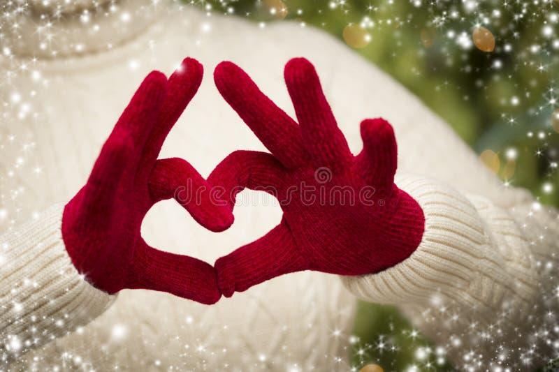 Mulher que veste os mitenes vermelhos que guardam para fora um sinal da mão do coração foto de stock royalty free