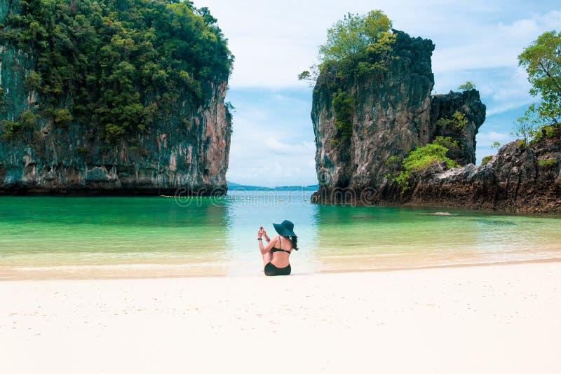 Mulher que veste um chapéu usando o telefone celular que toma uma foto na praia nas férias imagem de stock royalty free