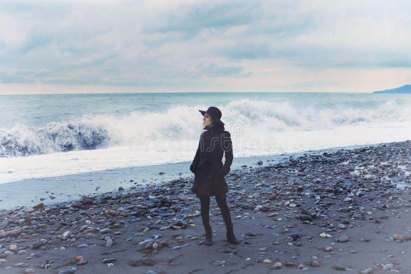 Mulher que veste um revestimento preto na praia fotos de stock royalty free
