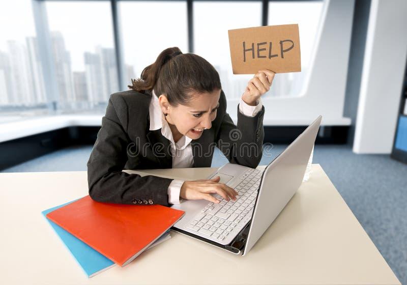 Mulher que veste um terno de negócio que trabalha em seu portátil que guarda um sinal da ajuda que senta-se no escritório moderno foto de stock royalty free