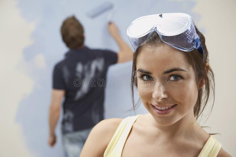 Mulher que veste vidros protetores com a parede da pintura do homem em casa fotografia de stock