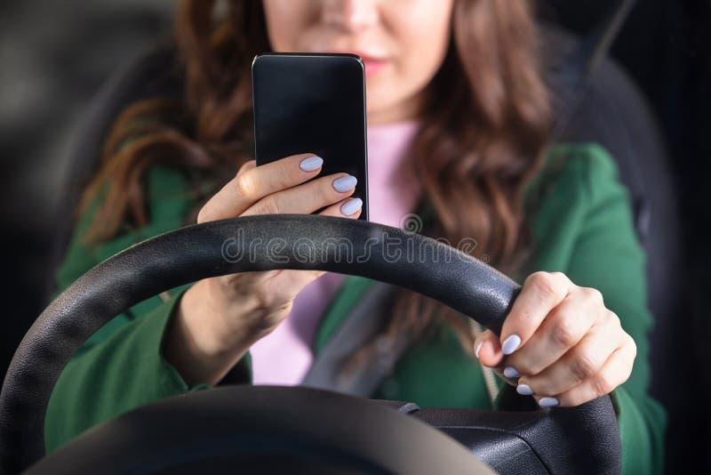 Mulher que viaja pelo carro usando Smartphone fotografia de stock royalty free