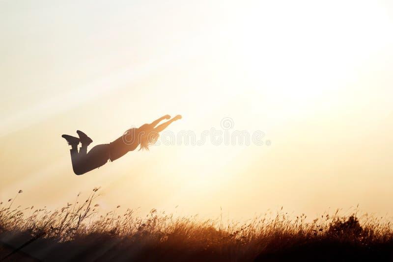 Mulher que voa sobre a natureza do prado no fundo da silhueta do por do sol imagens de stock