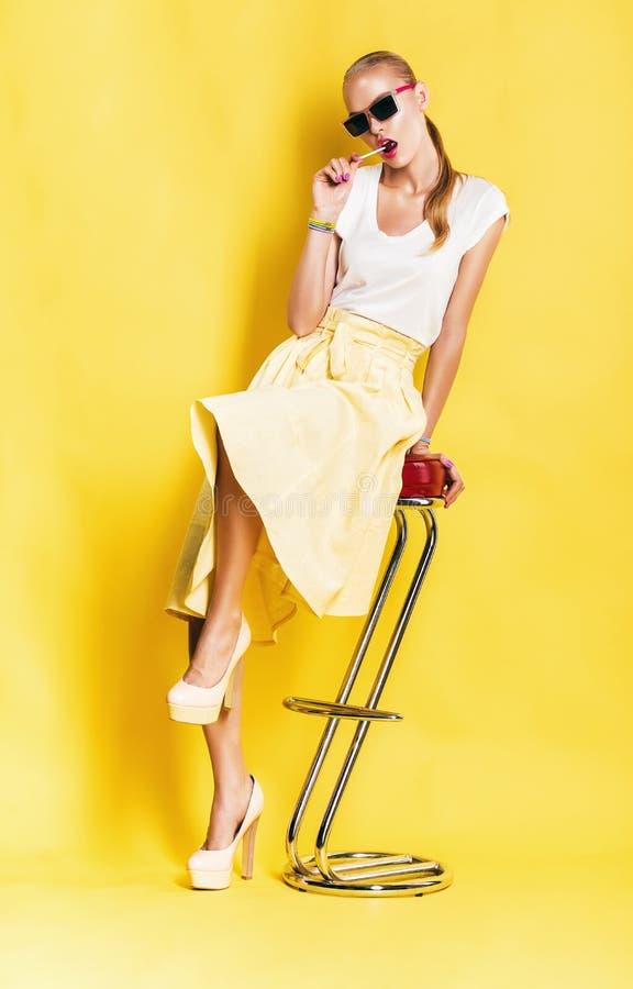 Mulher quente na saia amarela com o pirulito que senta-se na cadeira imagem de stock