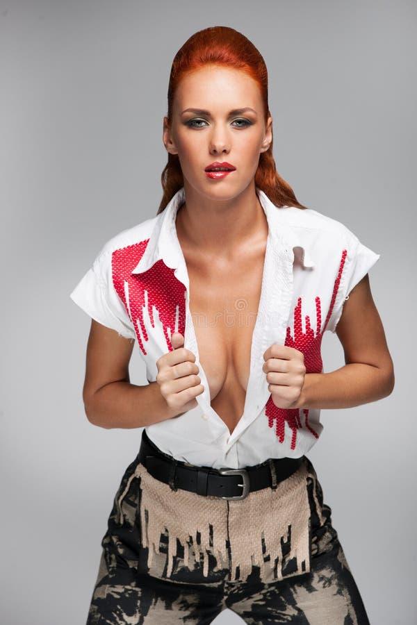 Mulher quente nova com a camisa aberta no fundo cinzento fotografia de stock