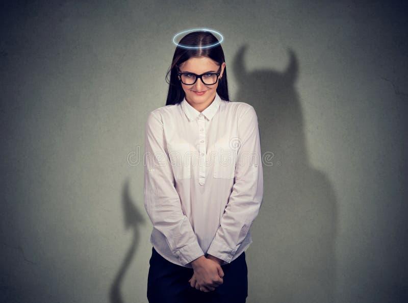 Mulher quieta tímida do anjo com caráter do diabo imagem de stock
