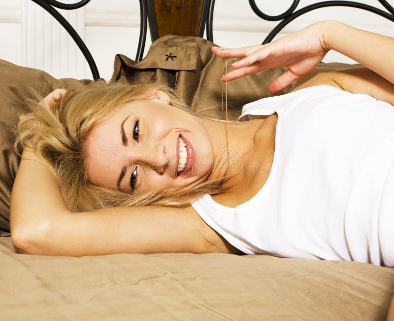 A mulher real consideravelmente loura dos jovens na cama cobriu o fim 'sexy' alegre de sorriso do olhar das folhas brancas acima, fotografia de stock