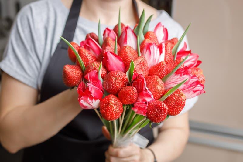 A mulher realiza em suas mãos um ramalhete original quase feito das tulipas e das morangos fotos de stock