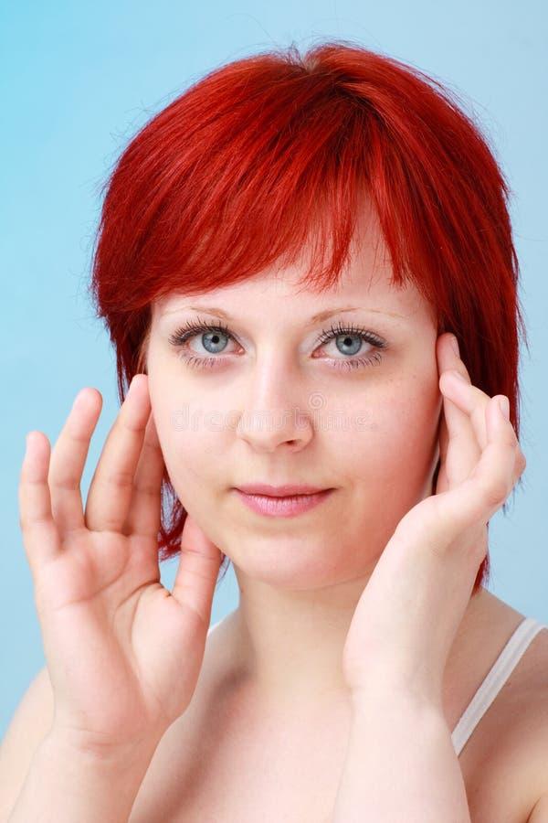 Mulher Red-haired em um fundo azul imagem de stock