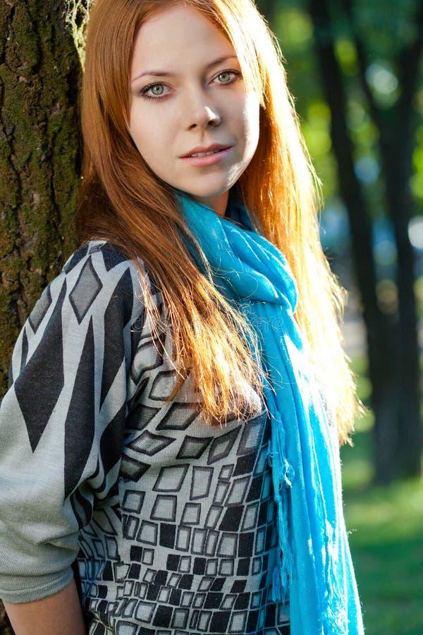 Mulher Red-haired perto da árvore imagem de stock