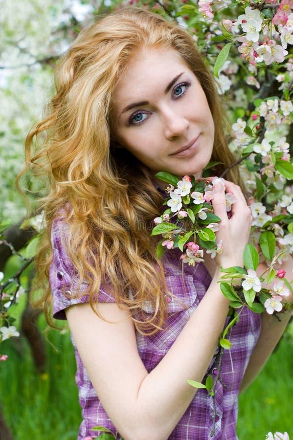 Mulher Red-headed sob a árvore de cereja fotos de stock