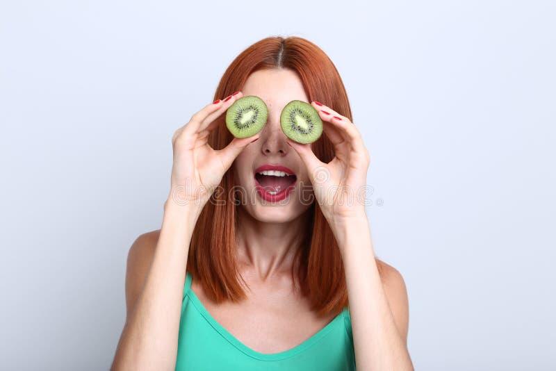 Mulher Redhaired com fruto de quivi fotografia de stock royalty free