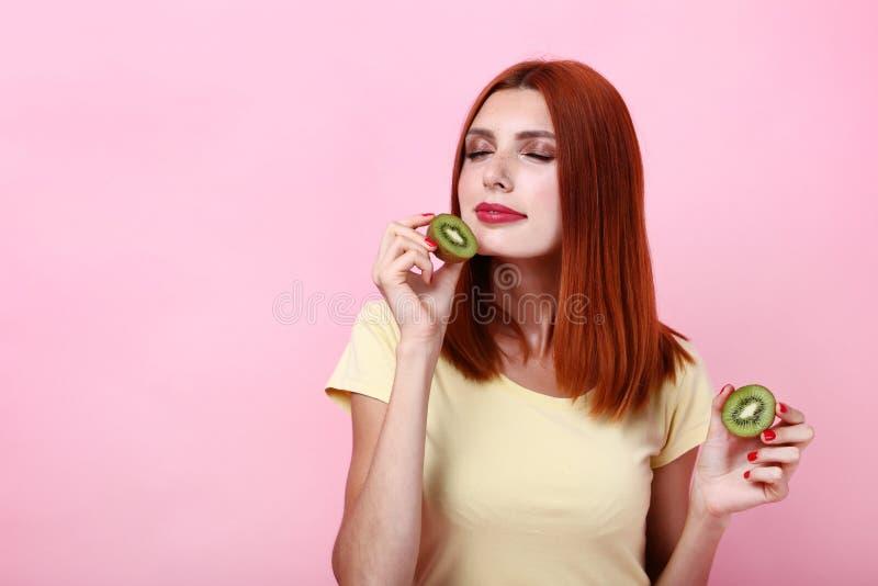 Mulher Redhaired com fruto de quivi imagens de stock