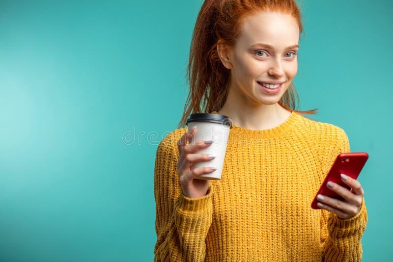 Mulher redhaired nova com café e smartphone sobre o fundo azul imagem de stock royalty free