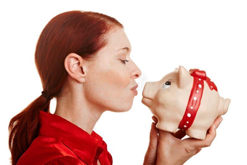 Mulher Redhaired que beija um piggy fotos de stock