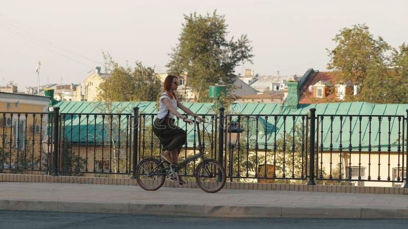 Mulher Redhaired que monta uma bicicleta na cidade em construções do fundo e em casa do telhado fotografia de stock