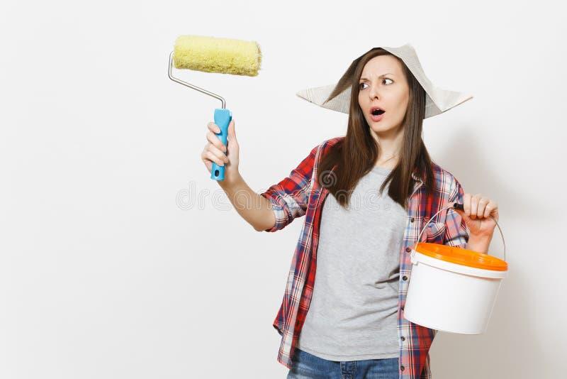 Mulher referida no chapéu do jornal que guarda o rolo de pintura para a pintura de parede e a cubeta vazia da pintura com o espaç fotografia de stock royalty free