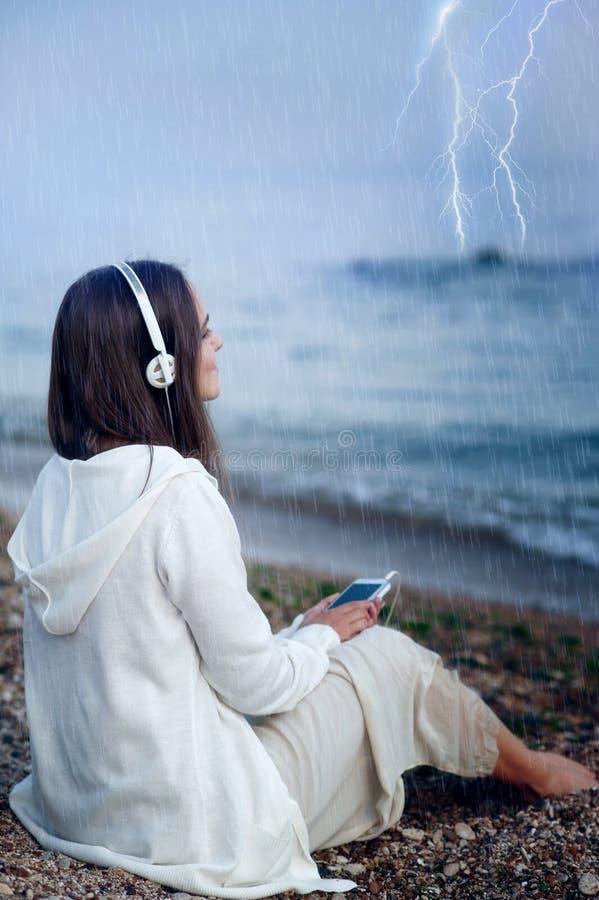 A mulher relaxa a música de escuta sob a chuva, sentando-se em uma praia do mar imagem de stock royalty free