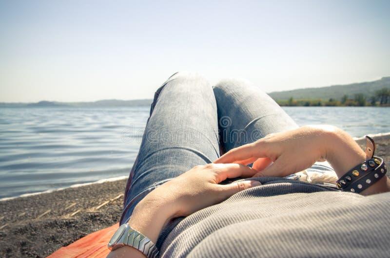 A mulher relaxa o encontro pelo lago imagens de stock royalty free