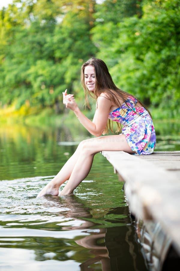 A mulher relaxa pelo lago que senta-se em um molhe de madeira imagens de stock