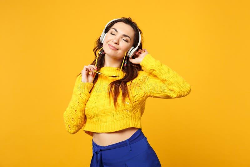 A mulher relaxada na camiseta, calças azul guarda a música de escuta dos óculos de sol com os fones de ouvido que mantêm os olhos fotos de stock royalty free