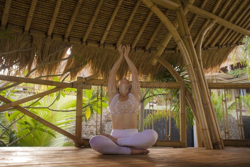 Mulher relaxado atrativa e feliz nova que senta-se na posição da ioga dos lótus que faz o ar livre da meditação e da concentração fotos de stock royalty free