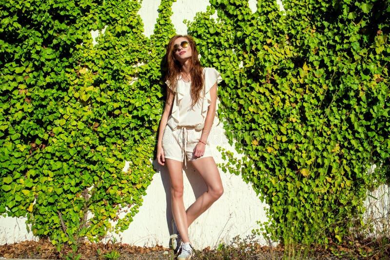 A mulher relaxado bonita no romper branco, nos keds e no círculo na moda espelhou os óculos de sol que estão na parede entrelaçad imagens de stock
