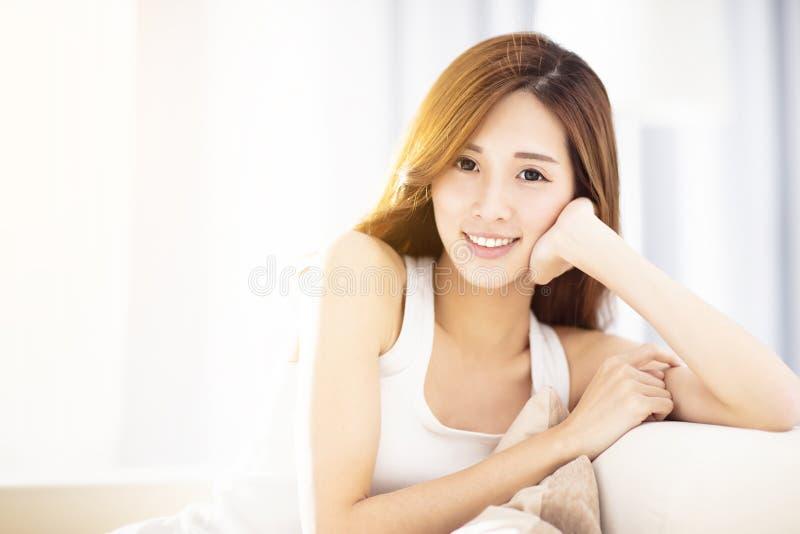 mulher relaxado bonita que senta-se no sofá imagem de stock