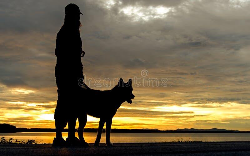 Mulher relaxado e cão de Silhoutte que apreciam o por do sol ou o nascer do sol do verão sobre o suporte do rio no lago próximo foto de stock