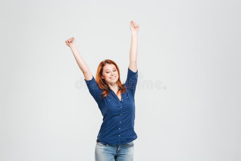 Mulher relaxado feliz que estica com os olhos fechados e mãos levantadas imagem de stock