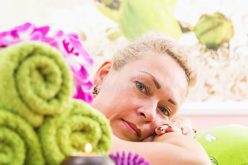 Mulher relaxado na tabela da massagem que recebe o tratamento da beleza em termas do dia fotos de stock