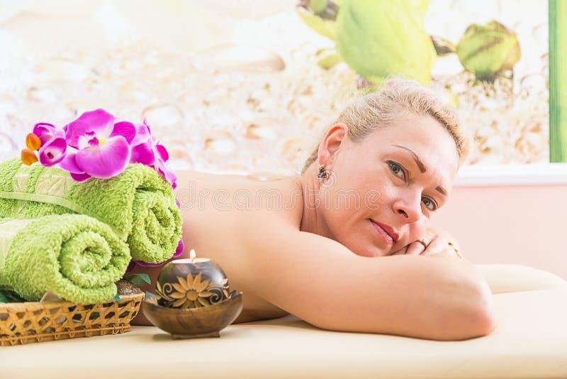 Mulher relaxado na tabela da massagem que recebe o tratamento da beleza em termas do dia imagem de stock