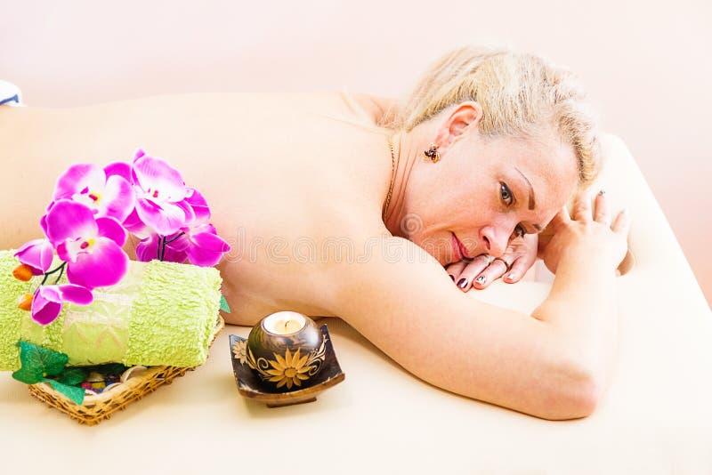 Mulher relaxado na tabela da massagem que recebe o tratamento da beleza em termas do dia foto de stock royalty free