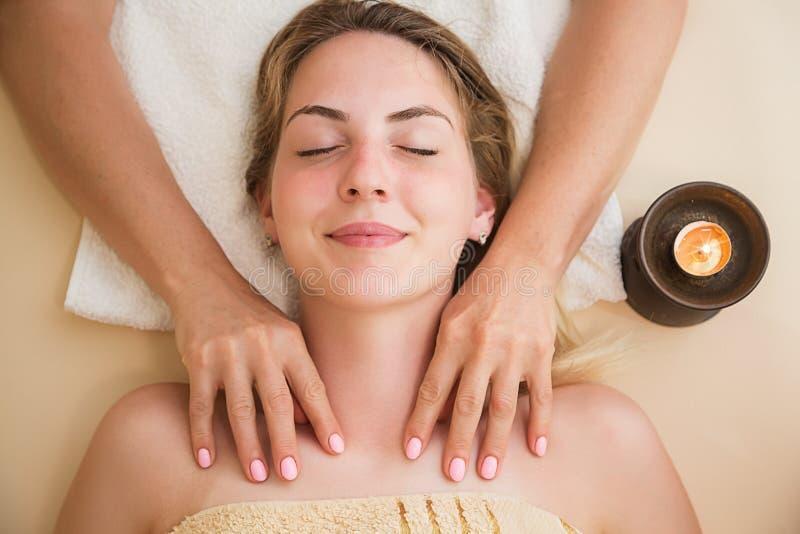 Mulher relaxado na tabela da massagem que recebe o tratamento da beleza em termas do dia fotografia de stock