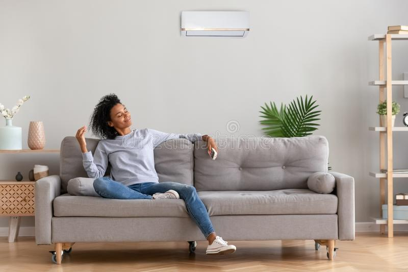 Mulher relaxado nova africana que senta-se no sofá que respira o ar fresco imagem de stock
