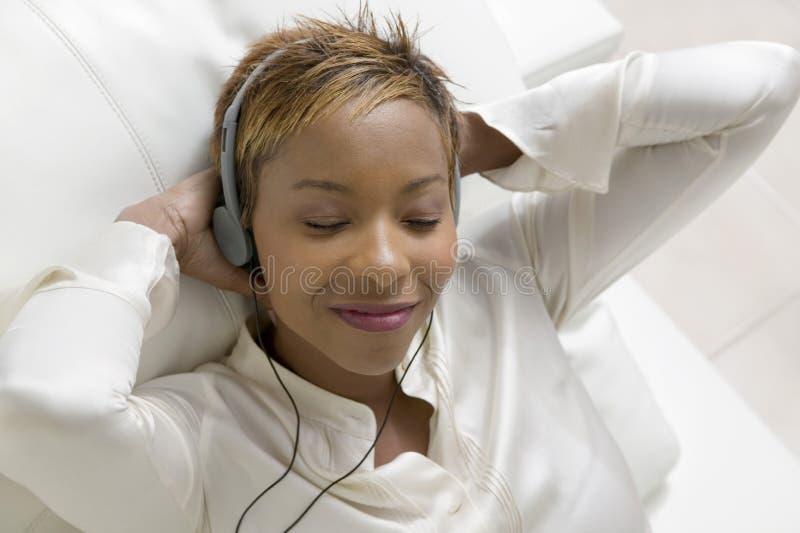 Mulher relaxado que escuta a música no leitor de cd portátil fotografia de stock