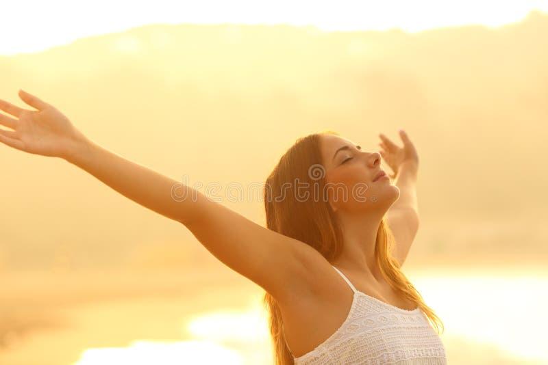 Mulher relaxado que estica os braços que respiram o ar fresco no por do sol imagem de stock royalty free