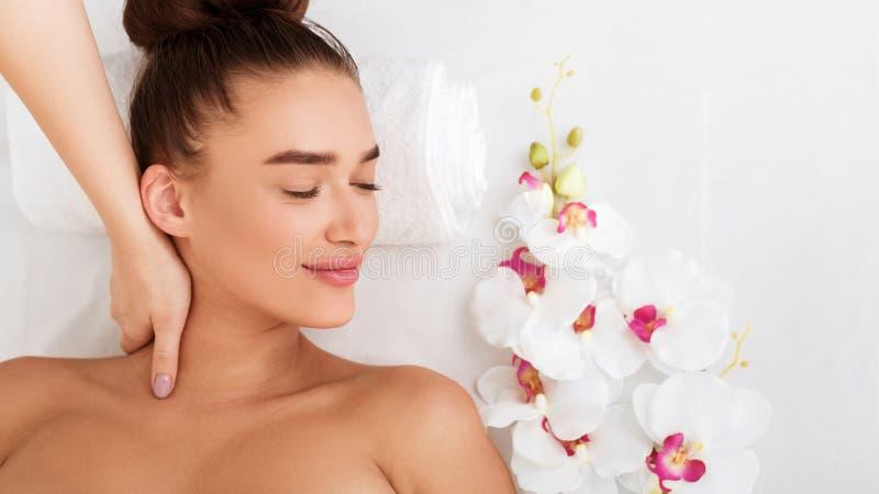 Mulher relaxado que recebe a massagem do pescoço na sala de estar de beleza fotos de stock