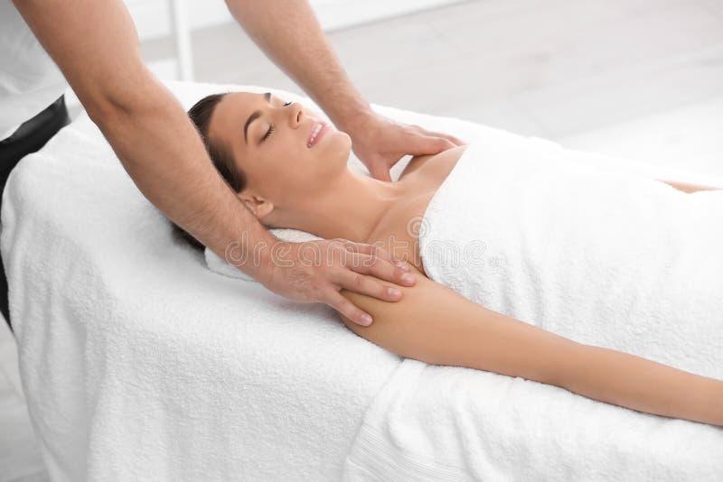 Mulher relaxado que recebe a massagem dos ombros foto de stock